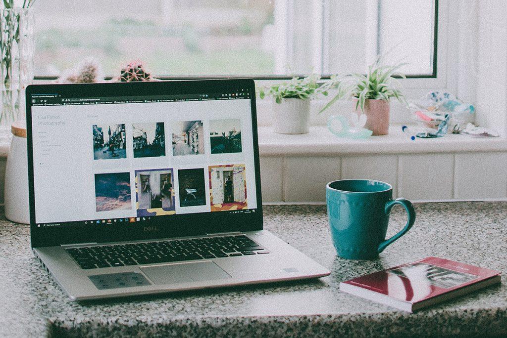 un portátil en una cocina con una taza al lado, representando el teletrabajo